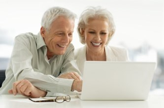 A mature couple looking happily at a computer